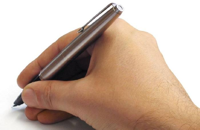 A right hand holding a silver pen
