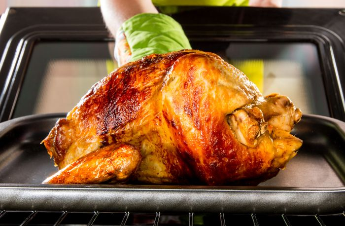 Roast-chicken-being-taken-out-of-oven