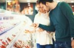 Couple looks at meat in supermarket.