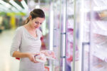 young-woman-looking at chicken in store