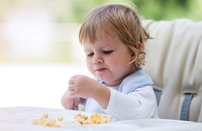 Baby eating eggs