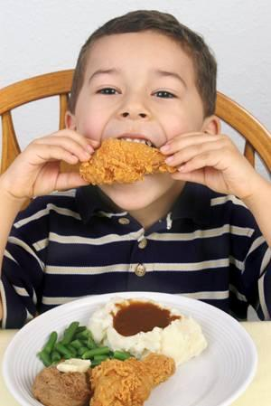 Kid eating chicken