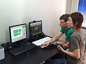 Two people are using OPP Farm's Mother program on a computer